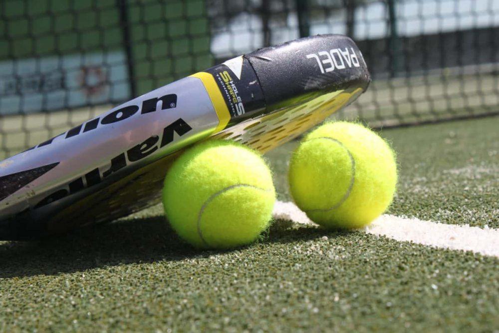 raqueta de pádel con dos pelotas
